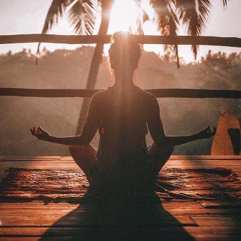 Meditáló nő pálmafákkal a háttérben